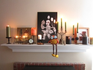 Our Fall (Halloween!) mantel. Not a leaf in sight, but we've got candles; original traditional and bizarre art; an assortment of tools; an old brass key; a petrol lamp; a bronze clock; an antique candelabra and a silly stuffed owl.