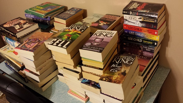 Piles of books on the desk in the guest bedroom.