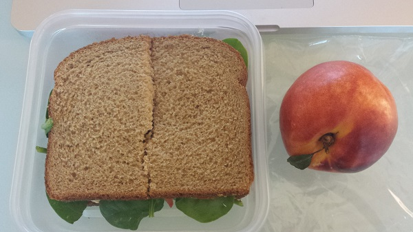 I ate lunch at my desk yesterday: Sandwich with Trader Joe's Mediterranean hummus, fresh spinach and Roma tomato on whole wheat bread... and a heavenly nectarine for dessert!