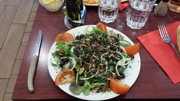 Salad in a restaurant (greens, tomatoes, onions, toasted walnuts)