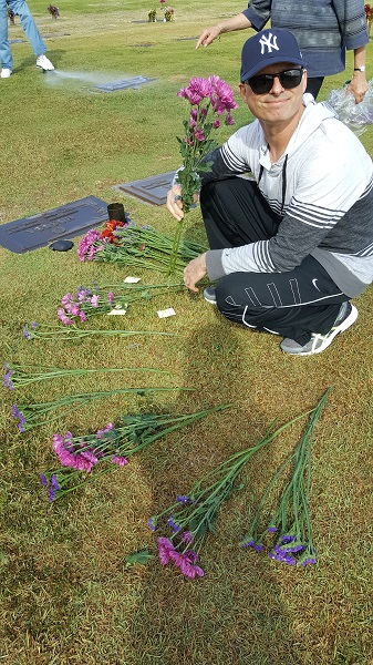 Callaghan sorting and arranging flowers for my Grandparents' graves.